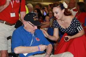 Pam, one of the 40's Bombshells, hands out chocolate bars to the vets as they start their journey through the parade route.