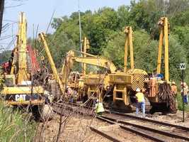 Crew work to upright derailed train cars.