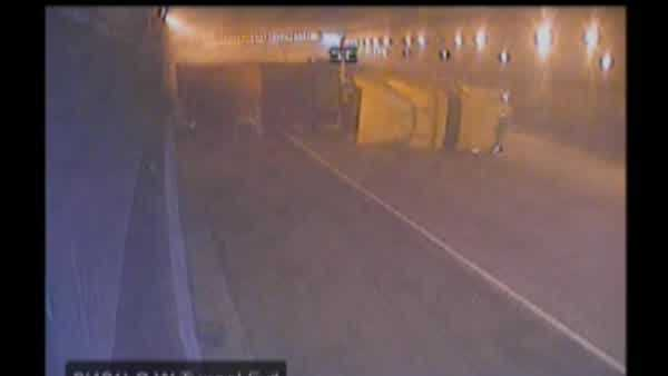 A semi tractor trailer rolled onto its side in the Mitchell Interchange tunnel, barely missing cars in front and behind it.