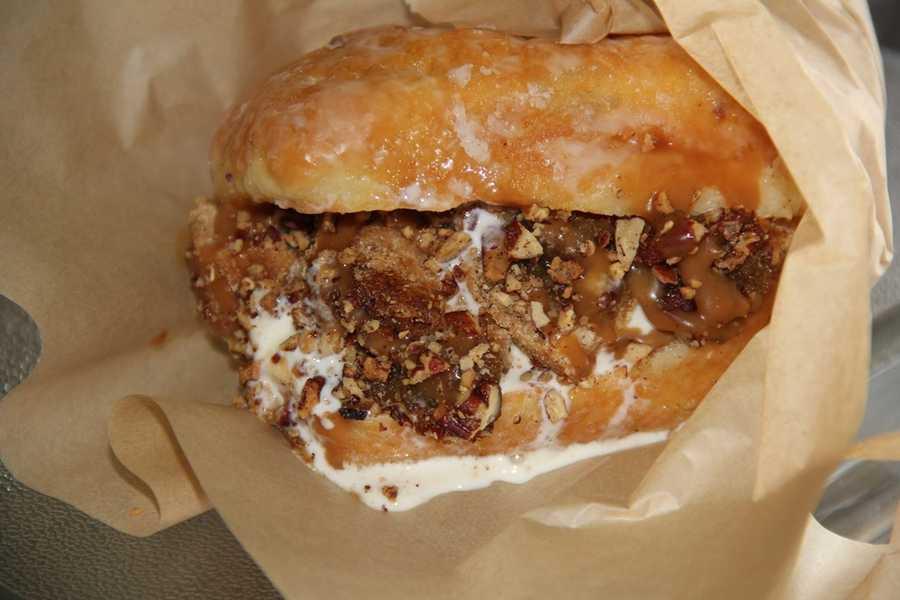 """P-Can Sam""- Pecan pie pieces, gooey caramel, pecans and custard inside a glazed doughnut."
