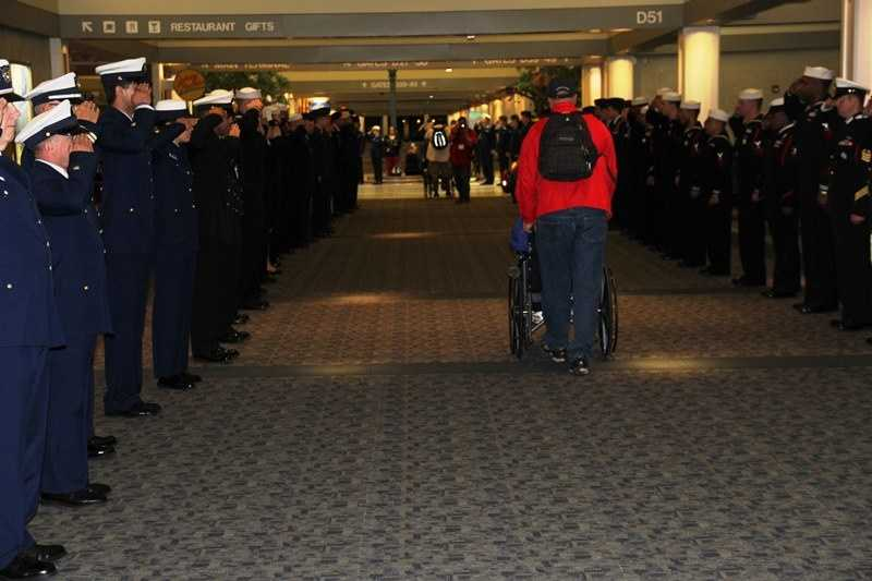 Active duty military line the concourse to welcome home the vets.