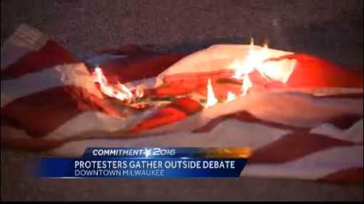 Protesters burned American flags in protest outside the Milwaukee Theatre.