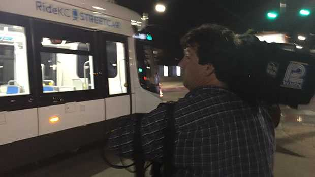 A KC Streetcar goes by as WISN 12 photojournalist Ed Ford sets up for a live shot during the 10 p.m. newscast.