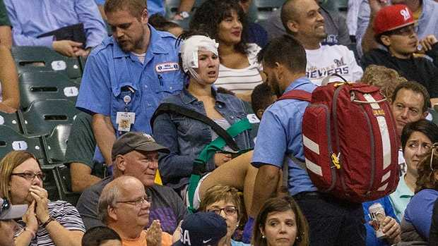 A woman, center, who was hit with a foul ball during a Milwaukee Brewers vs. Colorado Rockies game is carried out by medical staff in the second inning of the baseball game Tuesday, Aug. 23, 2016, in Milwaukee.