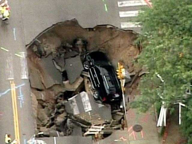 A Cadillac Escalade SUV was swallowed in large sinkhole many times its size at the intersection of Oakland and North Avenues on Milwaukee's East Side.