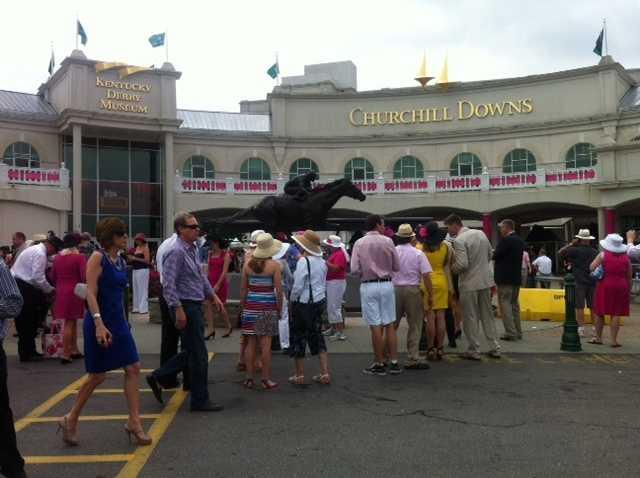 Fashionable Oaks-goers gather outside Churchill Downs.