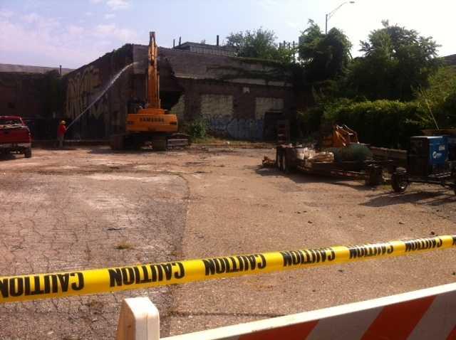 Crews began demolishing several decaying, contaminated buildings along East Main Street Monday.