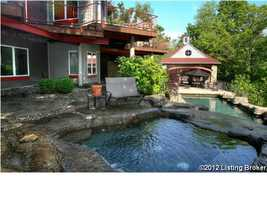 The pool area features a stone finish, pool, and hot tub.