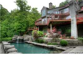 The back of the home features a wrap around tier porch leading down to the pool.