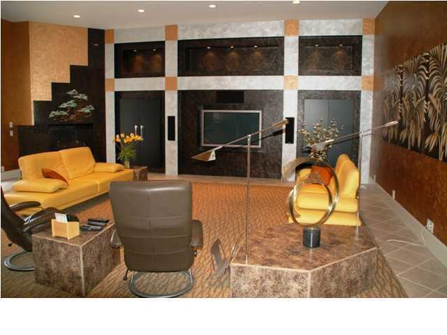 Bright-colored, leather sofas and custom-built entertainment system set a unique tone to this living room area.
