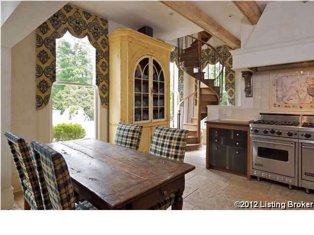 This alternate view of the kitchen allows you to see the windows and winding staircase.