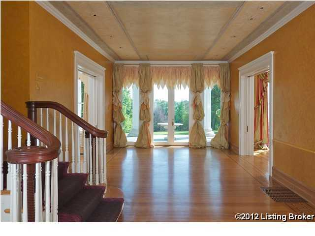 Double french-doors at the end of this home's entrance lead you outside to the property's beautiful acres.