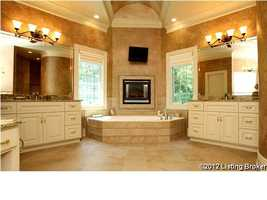 Master bathroom features a wrap around shower and garden tub with it's own fireplace.