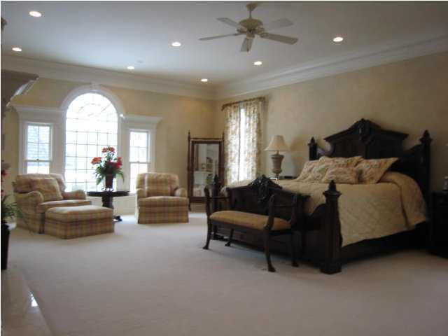 This spacious master bedroom is one of 4 bedrooms in the home and is illuminated by beautiful windows.