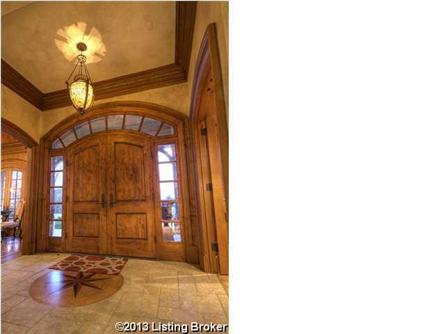 The foyer really makes a statement because of it's marble tiled floors with custom art piece and double wooden doors.