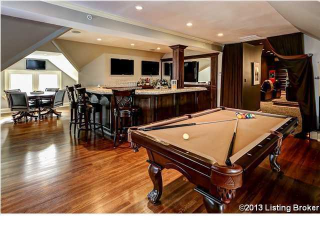 Remodeled basement makes for a huge entertainment room complete with multiple TVs, a pool table and a wet bar.