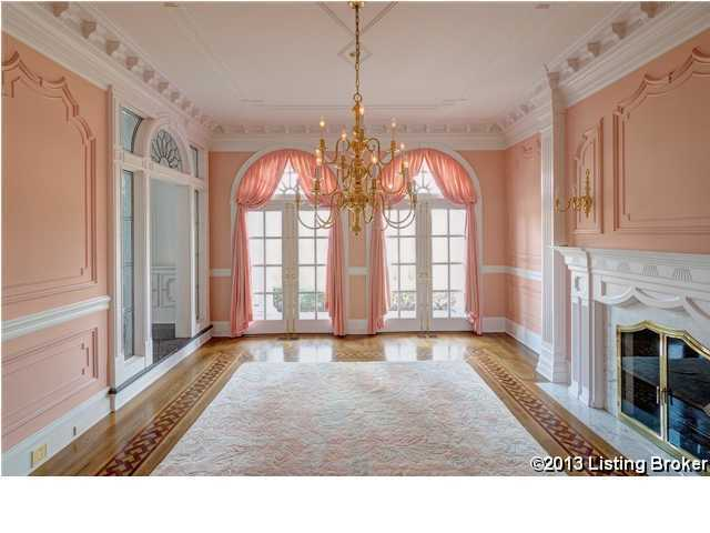 Formal dining area with grand chandelier and fireplace.