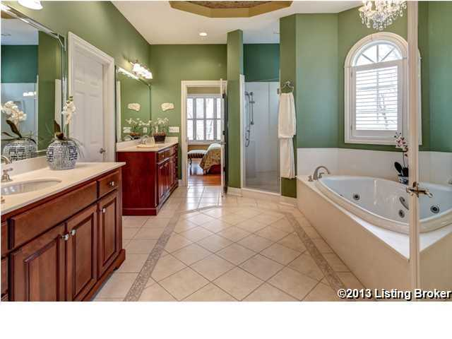 Giant master bedroom has a large spa tub separate from the standing shower quarters. His and her sinks with individual counter, cabinets, and vanities as well.