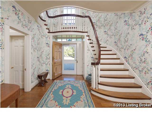 Blooming floral wallpaper cascades the foyer and winding staircase.