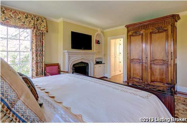Alternate view of the bedroom shows the shelving, fireplace, and entrance.