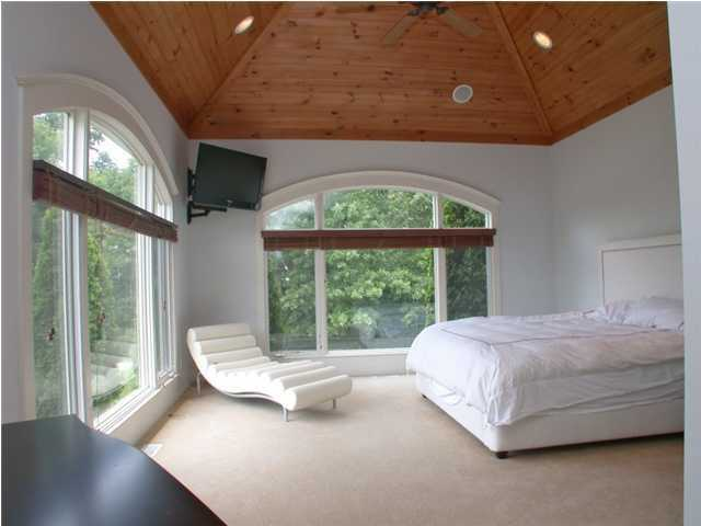 This third ceiling bedroom features floor to ceiling windows to let in loads of natural light.