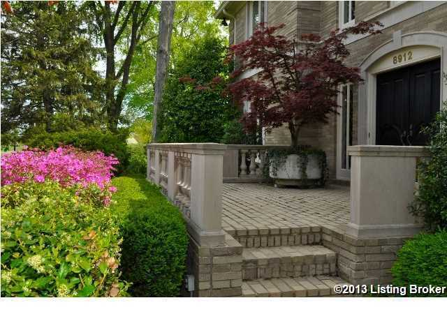 The lawn and landscape has been groomed to perfection surrounding the brick, castle-like, home.