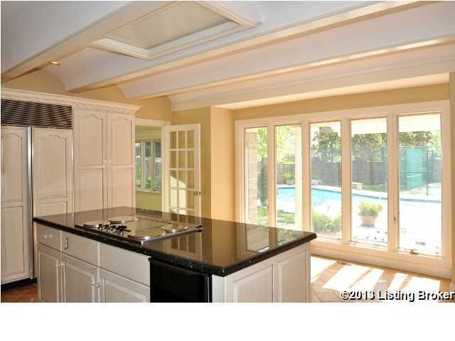 This huge kitchen features modern appliances, custom cabinetry and pool views.