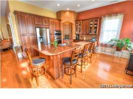 Beautiful kitchen, featuring custom cabinetry, granite counter tops, and seating for four.