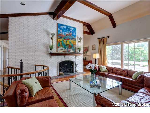 At the top of the spiral staircase is this comfortable living room which also features a bricked fireplace.