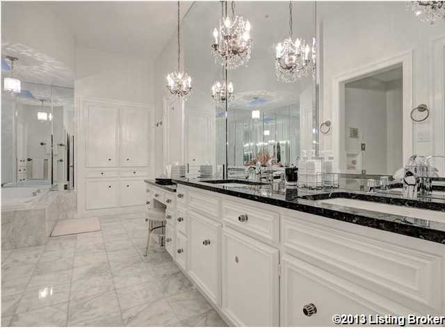 Master bathroom is simply immaculate. It features his and her sinks, a vanity space, and chandeliers.