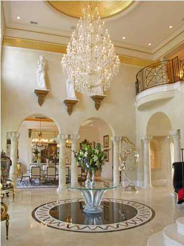 The foyer features a gold painted dome and stunning chandelier.