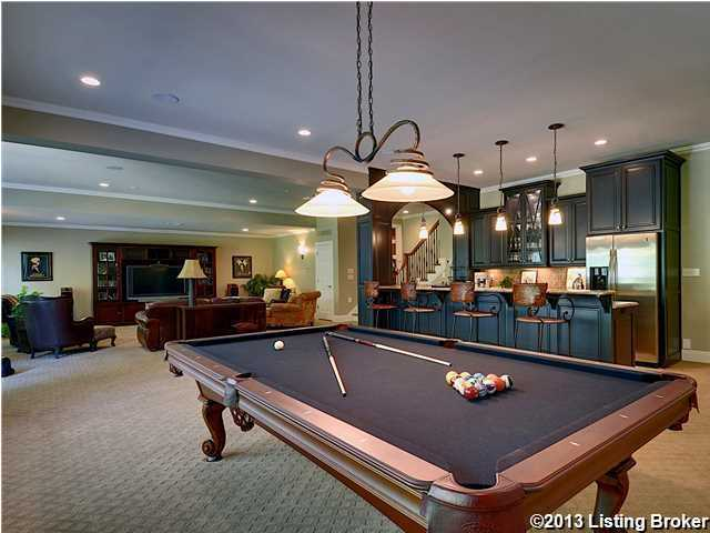 The basement is ready for game time! This game room features a kitchen, bar seating, pool table and big screen entertainment unit.