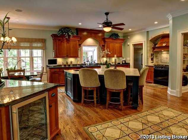 This large kitchen features a spacious island with seating and a dining bar table.