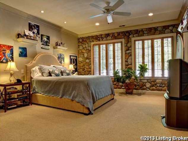 This masculine suite features a river stone wallpaper surrounding the windows.
