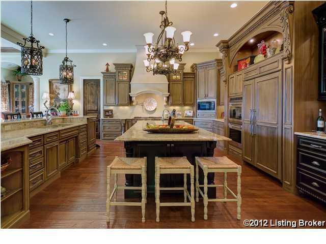 Custom glazed-finish cabinetry, pendant lighting over granite-topped islands, and wide plank flooring are among the amenities of this gourmet kitchen.