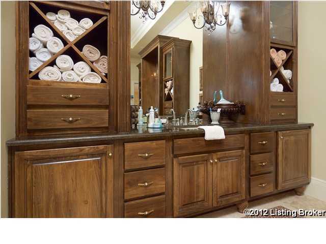 A lush bath with travertine flooring and granite vanity tops.