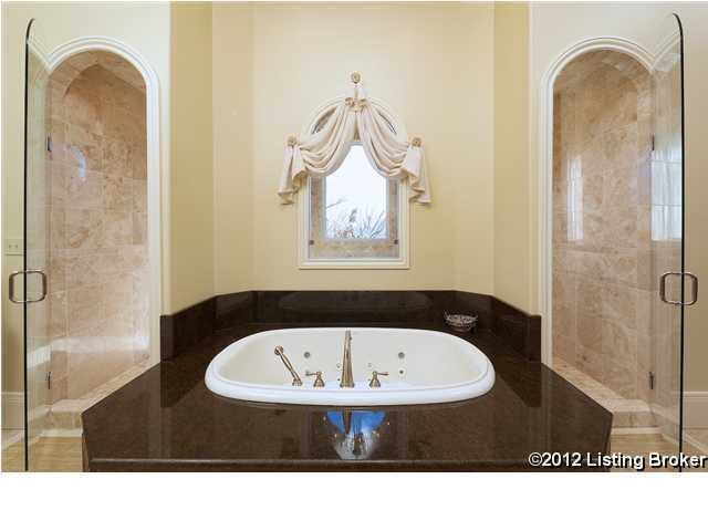 A jetted tub surrounded by a huge shower with two sets of body sprays, rain heads and hand-held steam showers.
