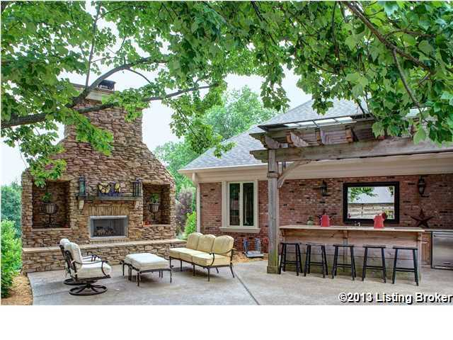 A fully equipped outdoor kitchen includes grill, sink and refrigerator with granite counter tops.