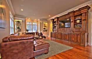 Custom entertainment unit and hardwood floors are presented in the family room.