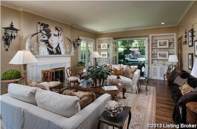 A stunning large living room allows natural light to stream in a multitude of windows and sets of French Doors.