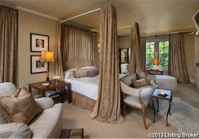 The master bedroom features a modern, canopy-style bed.