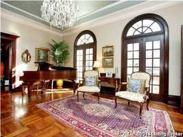 Towards the end of this formal living room, is a spectacular crystal chandelier and piano.
