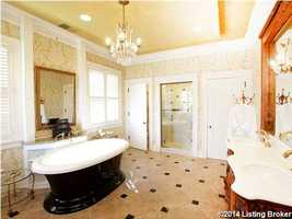 The bathroom continues to a beautiful shower scene and a dual vanity sink.
