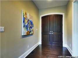 Dark wooden, double-doors lead into the master bedroom.