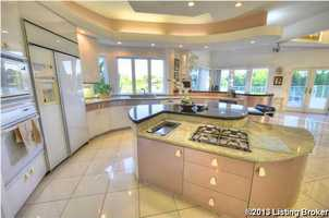 The kitchen features more lake views and beautiful custom curved cabinets, and granite counter-tops.