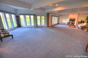 The huge great room has gorgeous custom built-in cabinetry and wall of glass that captures amazing panoramic views of the lake.
