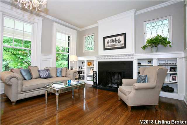 The charming living room features a contrasting fireplace and large windows.
