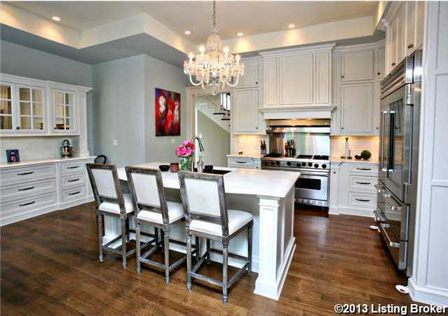 The large eat-in kitchen features a huge, marble-topped cooking island.