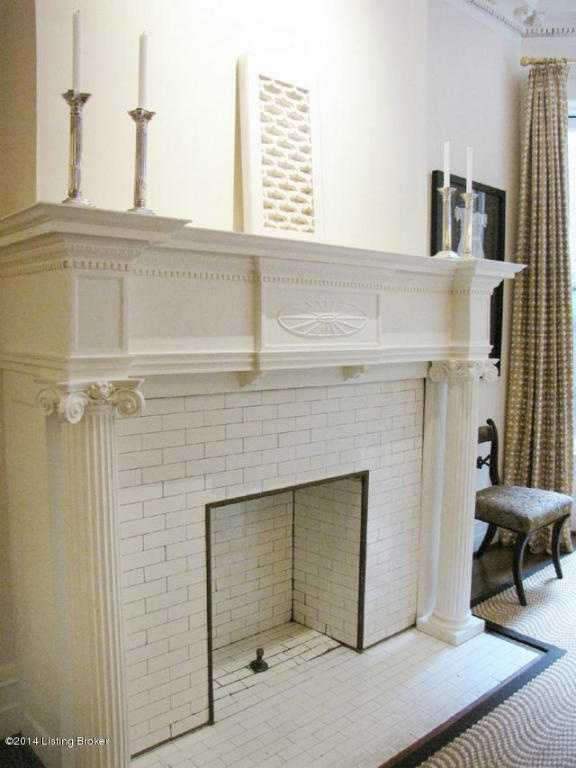 This restored fireplace and mantle has been painted off white.