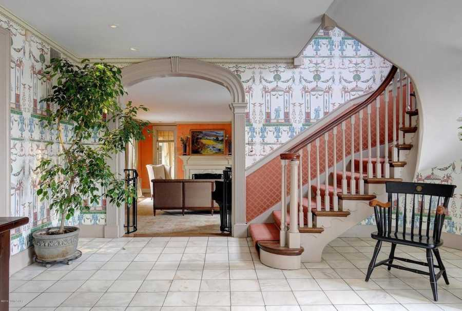 Once stepping inside, you'll be welcomed by a wide, light-filled foyer. It leads you to the formal living room or up an enchanting, curved staircase.
